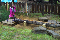 child playing in water sluiceway in an inclusive playground