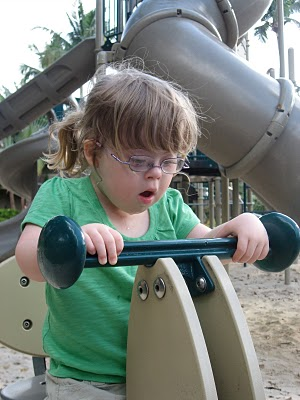 Penny plays on accessible playground equipment