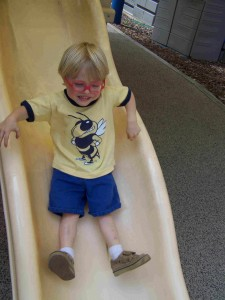 child with visual impairments goes down the slide