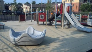 children with autism enjoy the omni spinner in this accessible playground